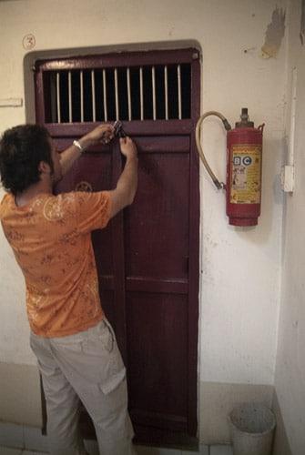 Cerrando el candado de la precaria puerta