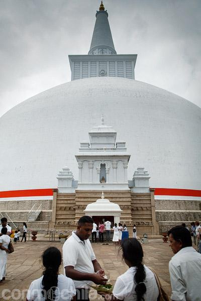 Devotos haciendo ofrendas frente a la stupa