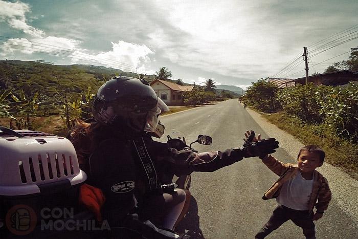 Itinerario de viaje a Laos: Imagen típica de los niños al salir del colegio y vernos con la moto
